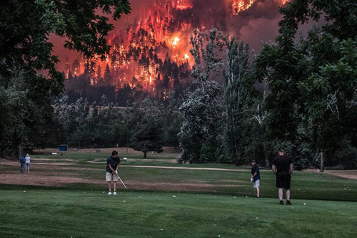 Golfers with forest fire burning behind them
