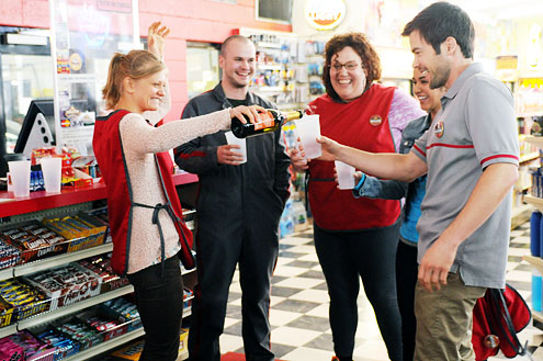 characters toasting each other with plastic cups in a convenience store
