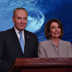 Chuck Schumer and Nancy Pelosi at the podium with a blue wave backdrop